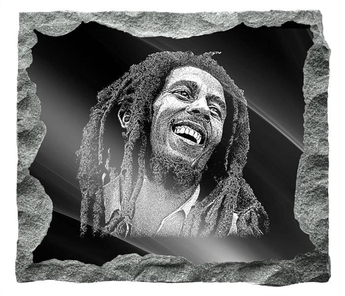 Memorial image of Bob Marley etched on a black granite background